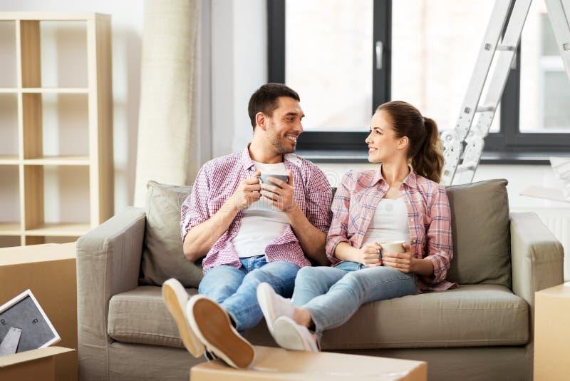 愉快的搬到新的家的夫妇饮用的咖啡 免版税库存照片