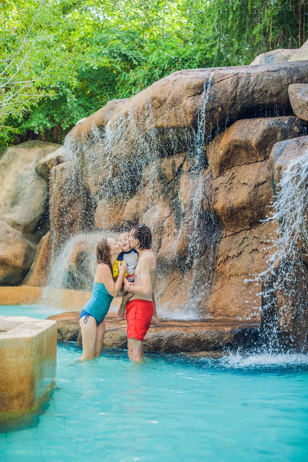 愉快的放松在aquapark的瀑布下的家庭母亲、父亲和儿子 库存图片