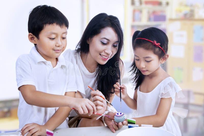 愉快的教师和学龄前儿童绘复活节彩蛋 库存照片