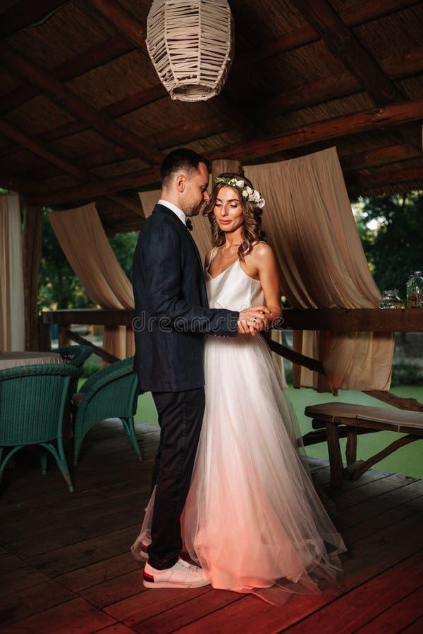 愉快的新娘和新郎和他们的第一个舞蹈,婚姻在有美妙的光和大气的典雅的餐馆 库存照片
