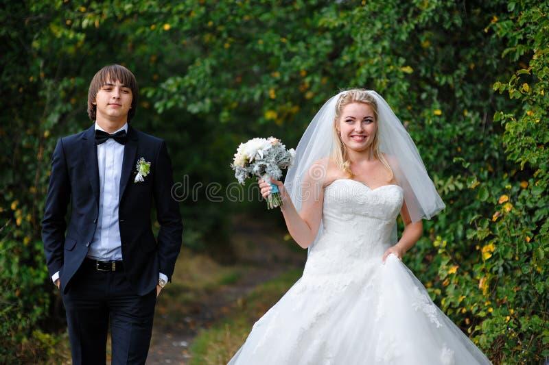 愉快的新娘和新郎在一个婚礼在夏天户外 免版税图库摄影