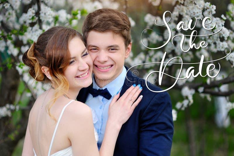 愉快的新娘和新郎在一个开花的春天庭院和词保存日期 书法字法 库存照片