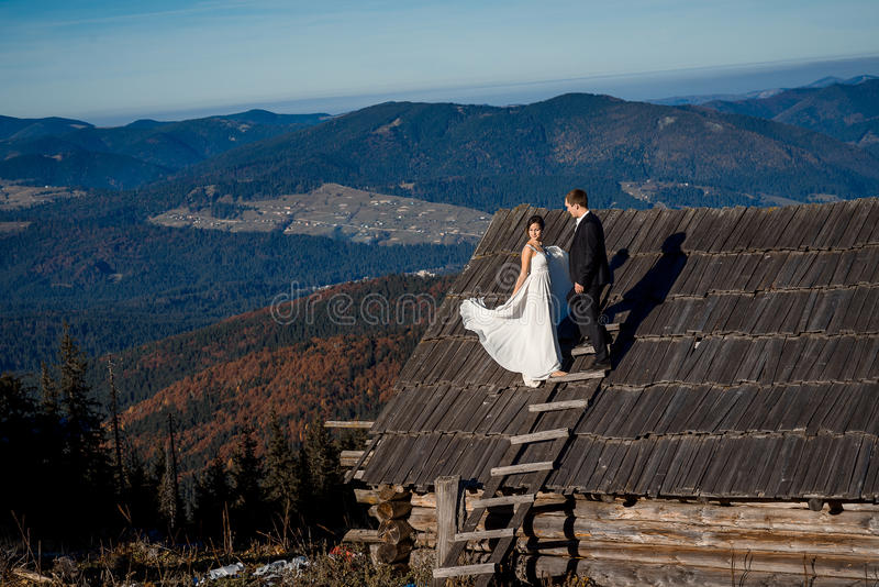 愉快的新娘和新郎在乡间别墅屋顶  惊人的山风景背景 图库摄影