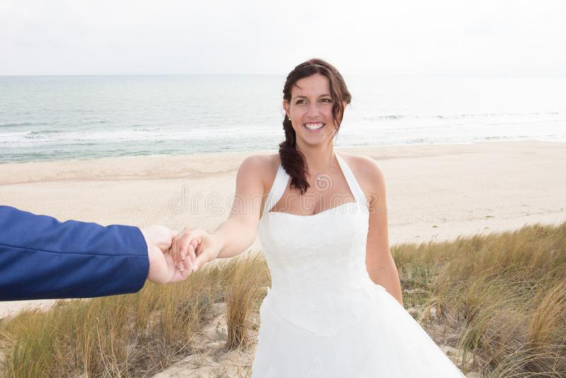 愉快的新娘和新郎在他们的拥抱在海滩的婚礼 库存照片