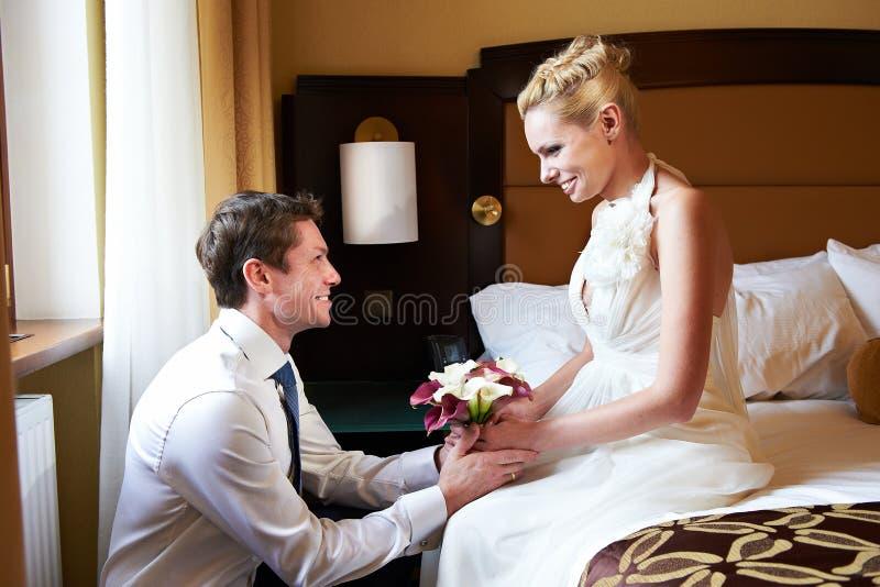 愉快的新娘和新郎在卧室 免版税图库摄影