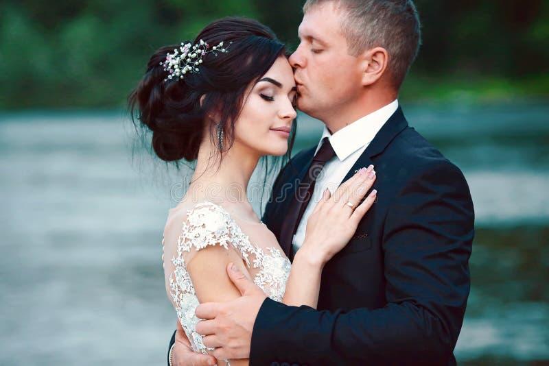 愉快的新娘和新郎在日落以后以一个蓝色晚上为背景在蓝色湖附近 免版税库存图片