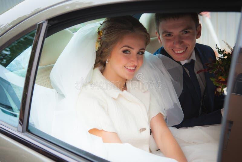 愉快的新娘和新郎在汽车 免版税库存照片