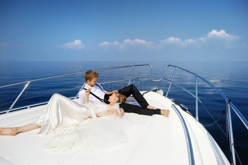 愉快的新娘和新郎在游艇 库存图片