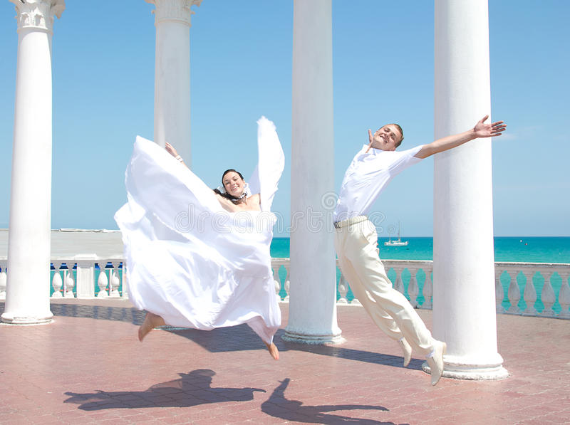 愉快的新娘和新郎在跃迁 免版税库存照片