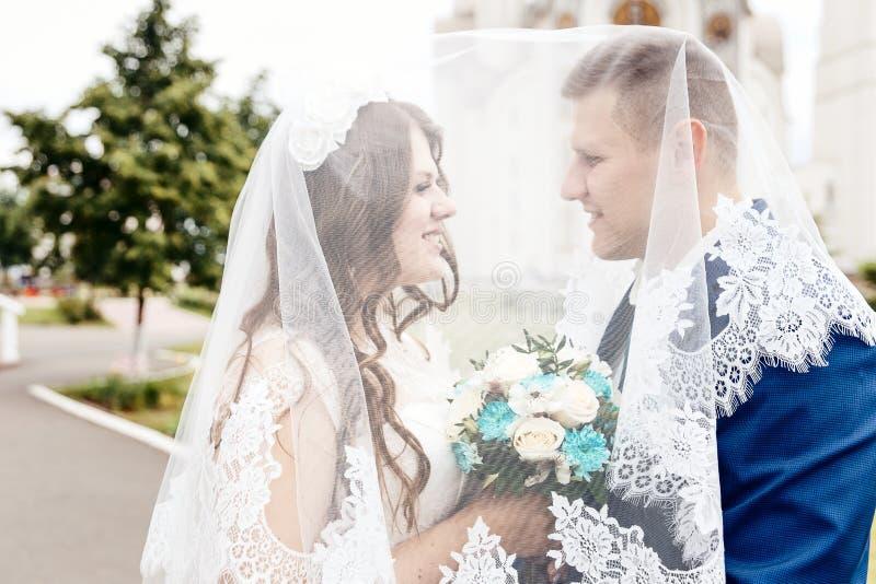 愉快的新娘和新郎在面纱下 库存图片
