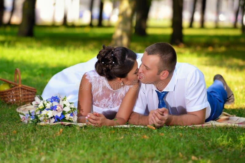 愉快的新娘和新郎在他们的婚礼在草说谎在公园和亲吻 免版税库存图片