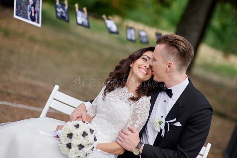 愉快的新娘和新郎坐长凳在公园 免版税库存照片