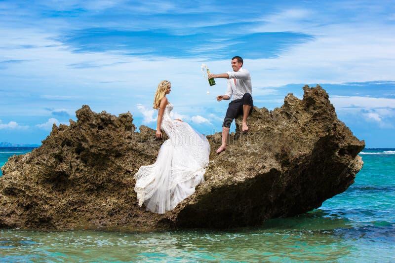 愉快的新娘和新郎获得在一个热带海滩的乐趣在p下 免版税库存图片