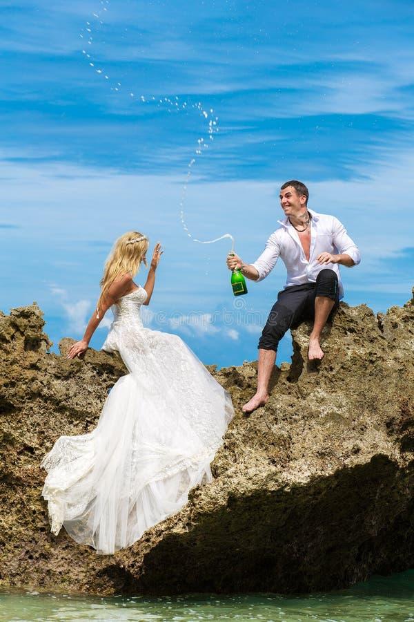 愉快的新娘和新郎获得在一个热带海滩的乐趣在p下 免版税库存照片