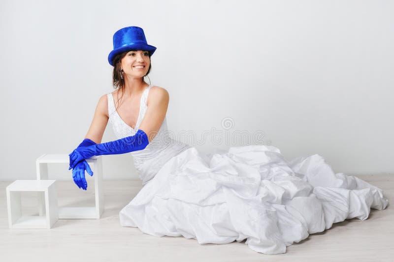 愉快的新娘坐在一个蓝色帽子的地板 库存图片