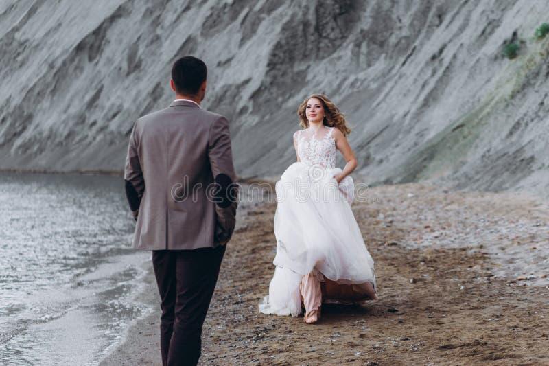 愉快的新婚佳偶夫妇 美丽的新娘和新郎在衣服 免版税库存图片