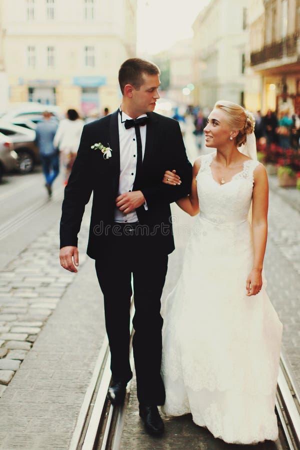 愉快的新婚佳偶沿电车轨道走在老城市 免版税图库摄影