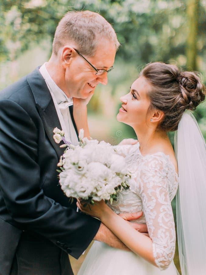 愉快的新婚佳偶的特写镜头旁边画象在庭院里 新娘抚摸新郎的面颊 库存图片