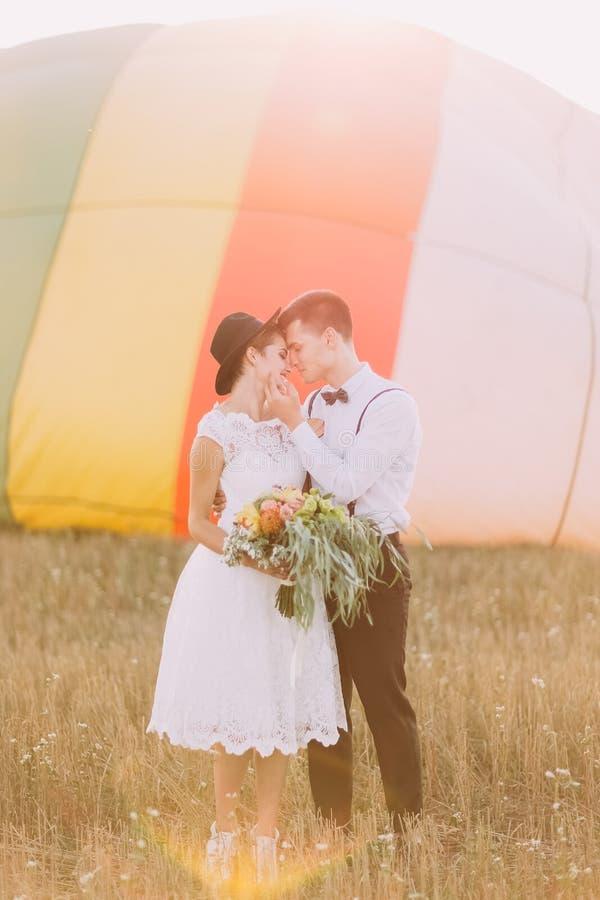 愉快的新婚佳偶站立势均力敌在airballoon的前面 新娘拿着婚礼花束 库存图片