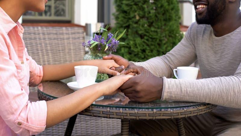 愉快的新婚佳偶谈话在结合在一起使手,饮用的早晨咖啡的咖啡馆 库存照片