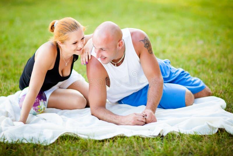 愉快的新成人夫妇在公园 免版税库存照片