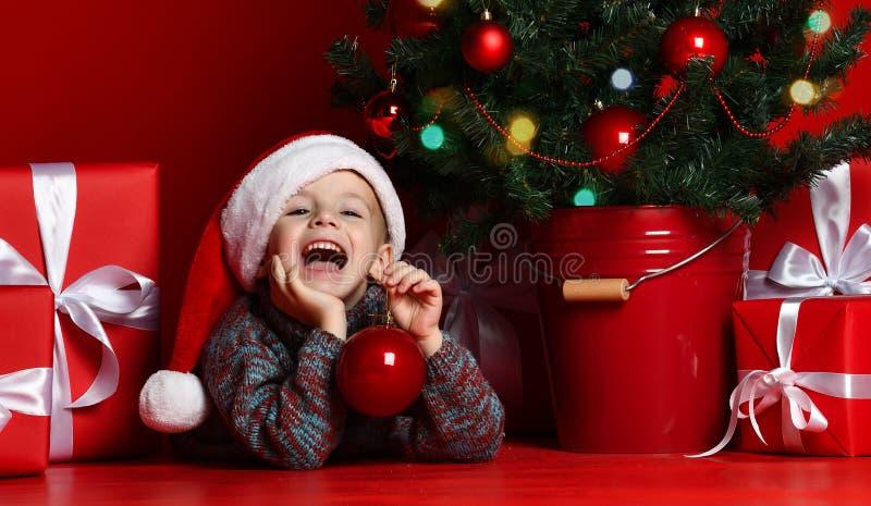 愉快的新的xmas年 孩子画象圣诞老人红色帽子等待的圣诞礼物的 库存图片