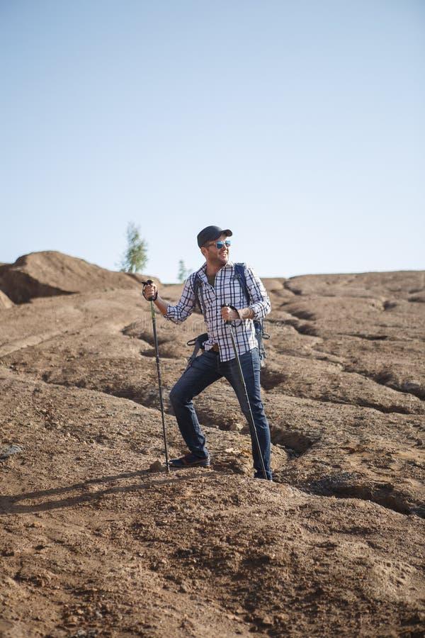 愉快的旅游人的图象用走的棍子在小山 库存图片