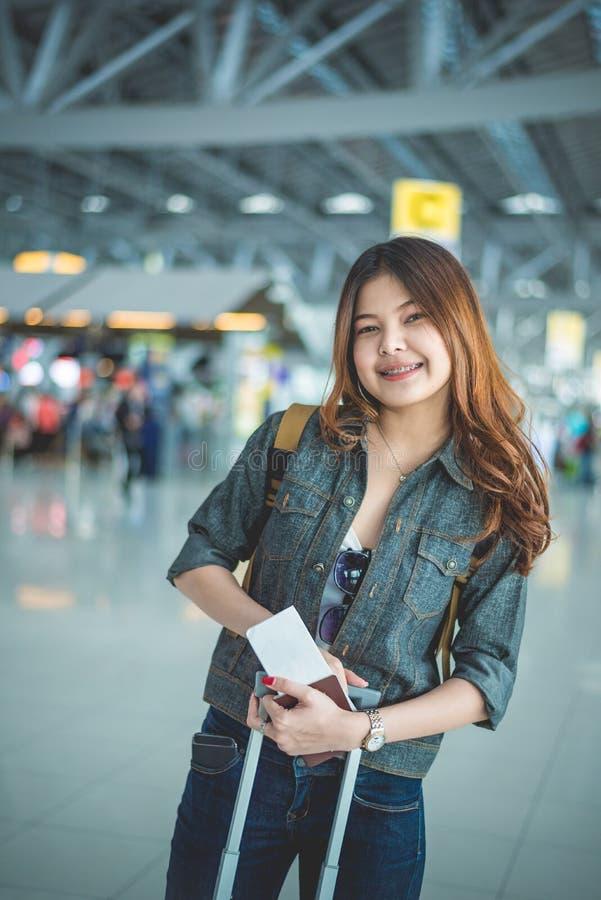 愉快的旅行和拿着在airpo的秀丽亚裔妇女手提箱 图库摄影