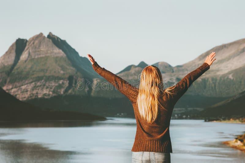 愉快的旅行妇女旅游手提高了享受挪威日落山和海风景生活方式概念冒险v 库存图片