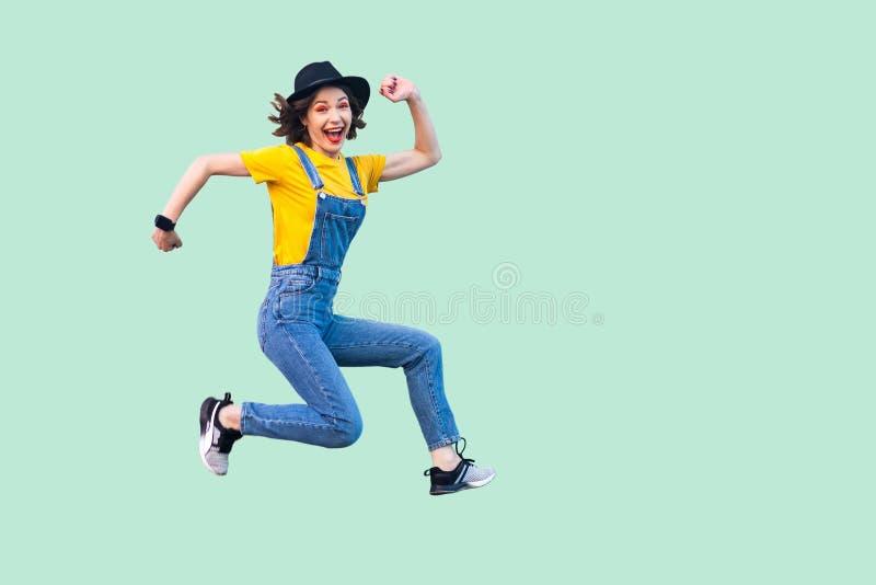 愉快的无忧无虑的俏丽的年轻行家女孩画象蓝色牛仔布总体的,黄色衬衣和黑帽会议跳跃,看照相机 免版税库存图片
