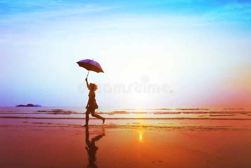 愉快的无忧无虑的女孩剪影有跳跃在海滩的伞的 库存图片
