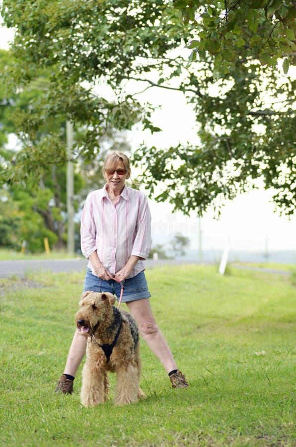 愉快的无忧无虑的妇女走的最好的朋友狗在乡下 免版税库存照片