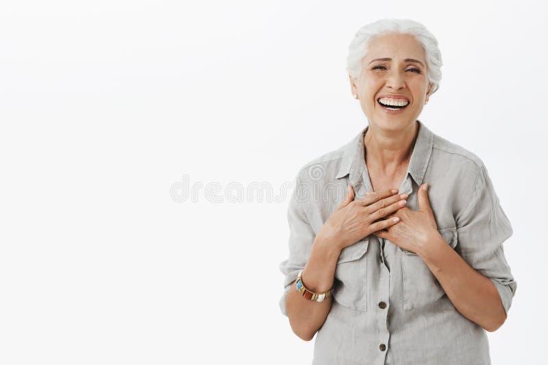 愉快的无忧无虑的老妇人满意对怎么生活去 有灰色头发的快乐的迷人的资深夫人在宽松衬衣 免版税库存图片