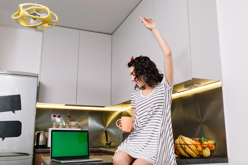 愉快的早晨在快乐的年轻女人的现代公寓的厨房里获得的礼服的在桌上的乐趣 有绿色的膝上型计算机 库存照片