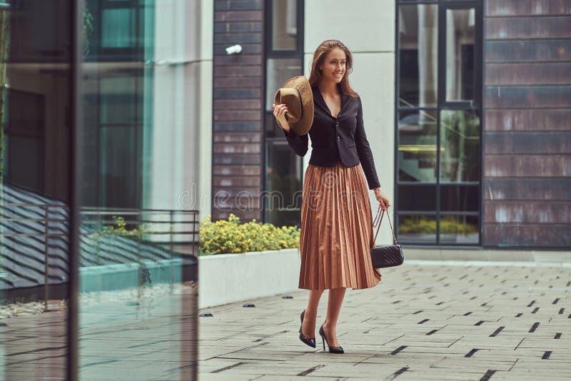 愉快的时尚端庄的妇女穿一件黑夹克的,棕色帽子和裙子有提包的抓住走在欧洲人 免版税图库摄影