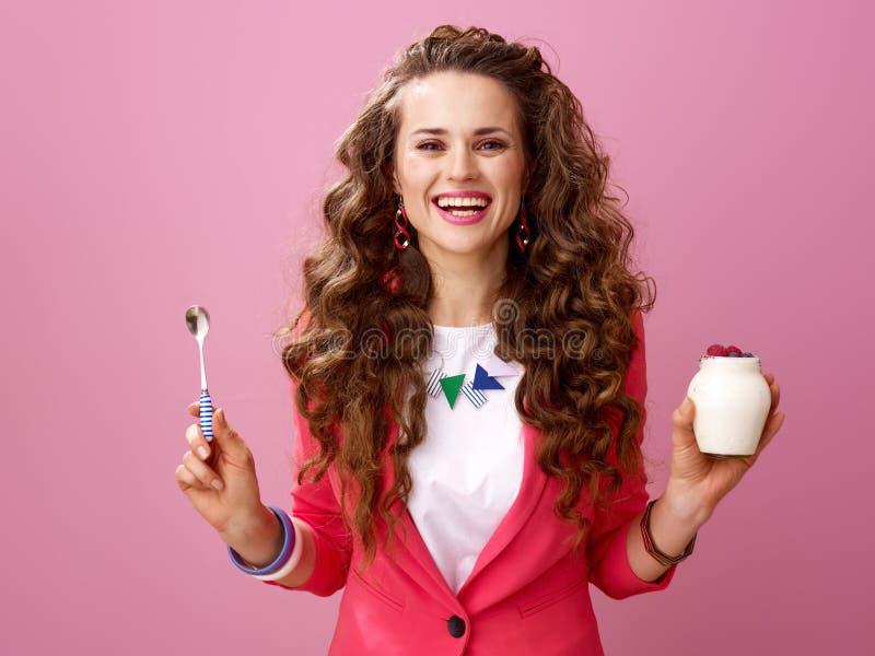 愉快的时髦妇女用农厂有机酸奶和匙子 库存图片