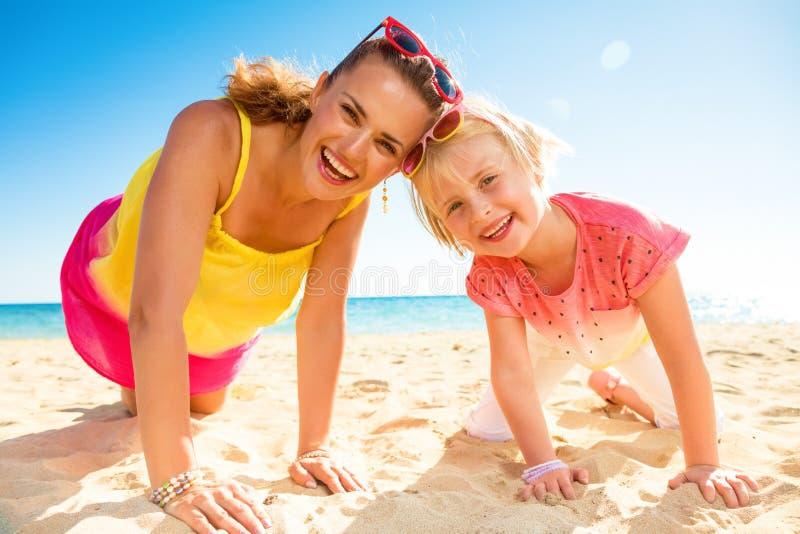 愉快的时髦母亲和女儿五颜六色的衣裳的在海滩 库存照片