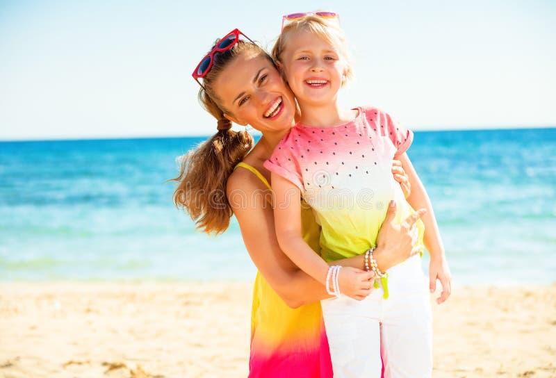 愉快的时髦母亲和孩子五颜六色的衣裳的在海岸 库存照片
