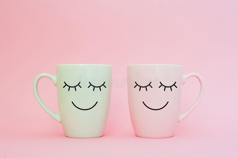 愉快的星期五词 两杯咖啡一起站立是在桃红色背景的心脏形状与在杯子的微笑面孔 免版税库存照片