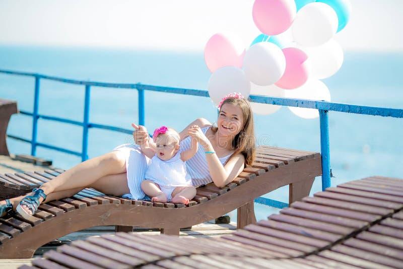 愉快的有五颜六色的气球的一起走在海滩的母亲和孩子在海附近 免版税库存照片