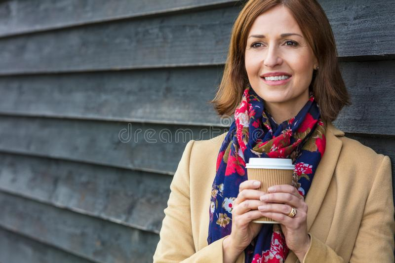 愉快的有吸引力的中世纪妇女饮用的咖啡 图库摄影