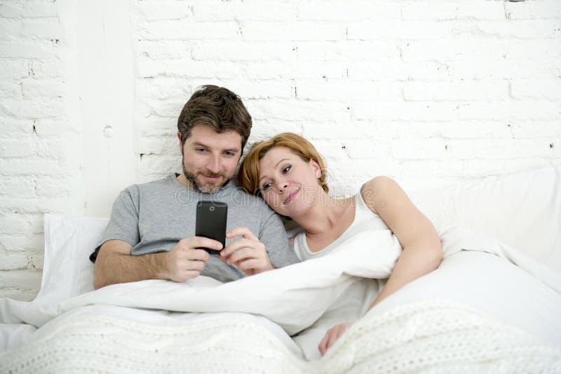 愉快的有吸引力的夫妇在使用微笑的手机的床上一起观看互联网app 免版税库存照片