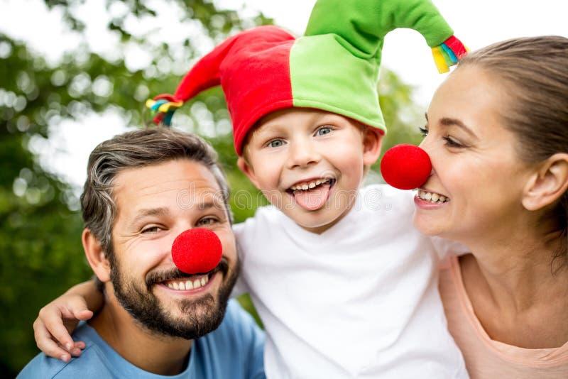 愉快的有父母的男孩佩带的傻瓜盖帽 免版税库存照片