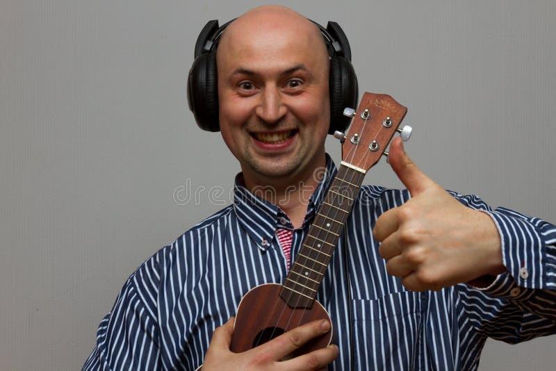 愉快的有耳机的人palying的尤克里里琴吉他 免版税库存照片