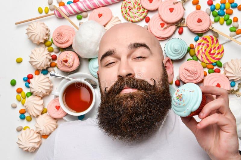 愉快的有胡子的在白色背景隔绝的人咬住的奶油蛋糕 免版税库存照片