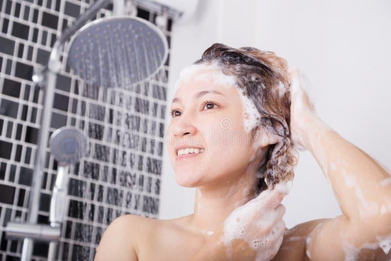 愉快的有香波和阵雨的妇女洗涤的头 免版税库存照片