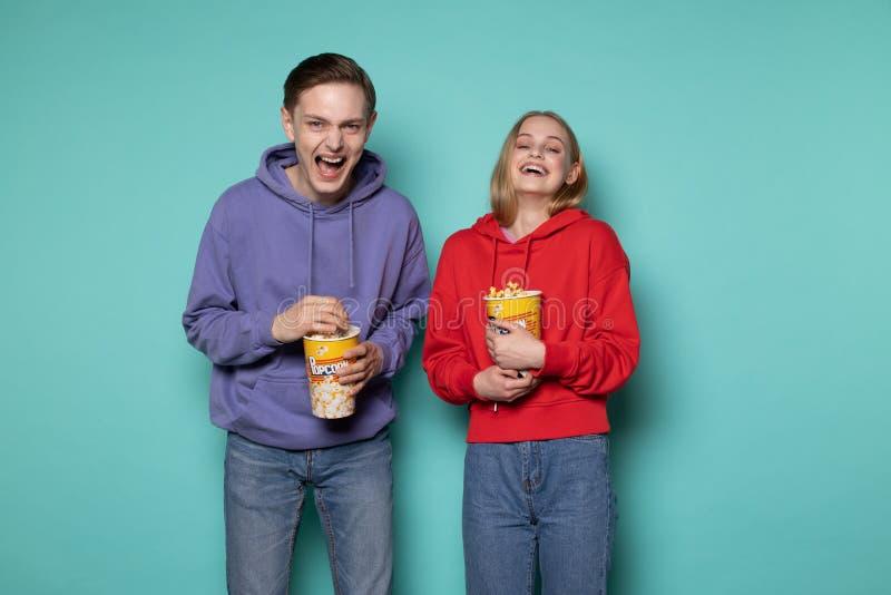 愉快的朋友、美丽的白肤金发的紫色有冠乌鸦的观看一部喜剧电影用玉米花的女孩和人在手上 库存图片