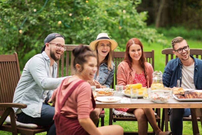 愉快的朋友吃晚餐在夏天游园会 免版税库存照片