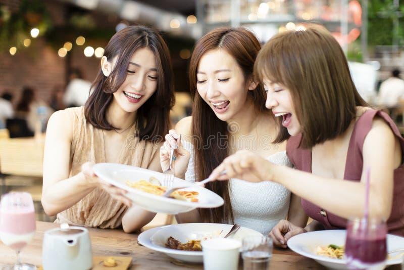 愉快的朋友吃晚餐在餐馆 免版税库存照片