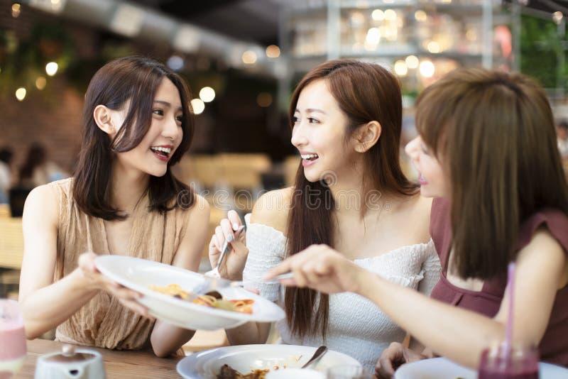 愉快的朋友吃晚餐在餐馆 图库摄影